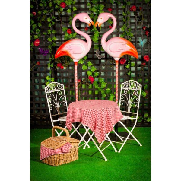Flamingo on pole with wrought iron garden furniture